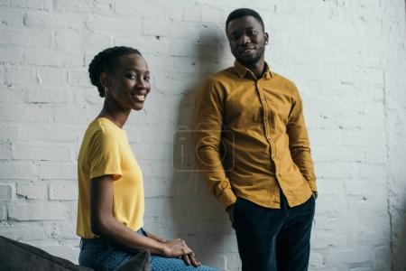 beautiful young african american couple in yellow shirts smiling at camera