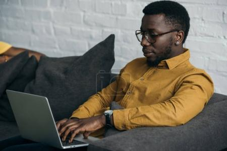 Photo for Handsome young african american man in eyeglasses sitting on sofa and using laptop - Royalty Free Image
