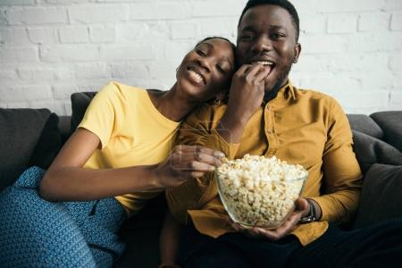 Photo for Beautiful happy african american couple eating popcorn while sitting on sofa at home - Royalty Free Image
