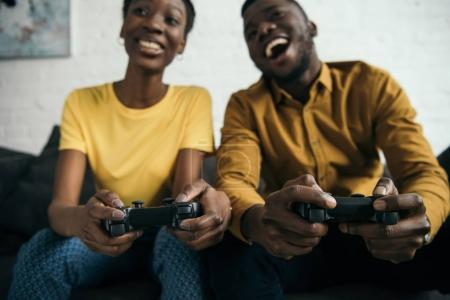 Photo for Happy young african american couple playing with joysticks together - Royalty Free Image