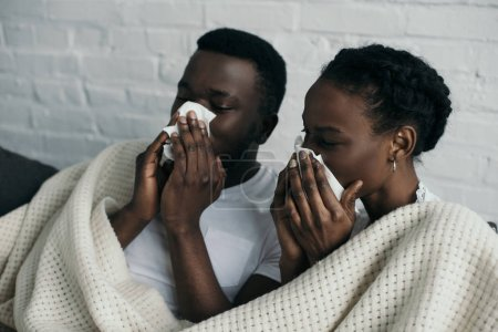 young diseased couple holding paper napkins and lying under blanket together at home