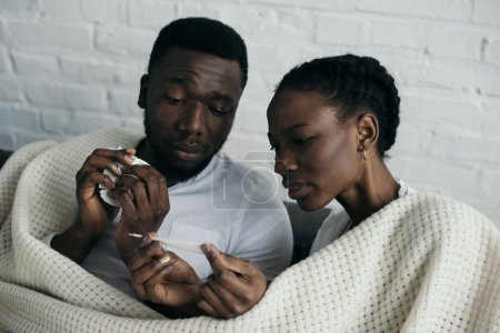 young african american couple checking thermometer while having flu together at home