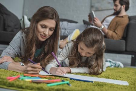 Photo pour Mère et fille dessinent sur le sol tandis que le père utilise une tablette sur le canapé dans le salon - image libre de droit