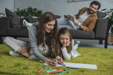Photo for Happy mother and daughter drawing on floor and father using tablet on sofa - Royalty Free Image
