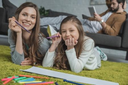 mother and daughter drawing on floor and looking at camera