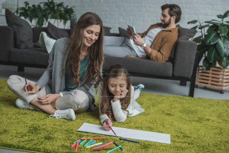 mother and daughter drawing on floor and father using tablet on sofa