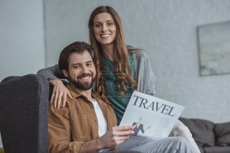 Photo pour Couple souriant assis avec journal de voyage et de regarder la caméra à la maison - image libre de droit