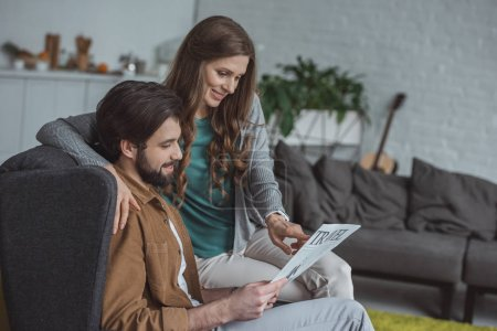 Photo for Side view of attractive couple reading travel newspaper and planning trip at home - Royalty Free Image