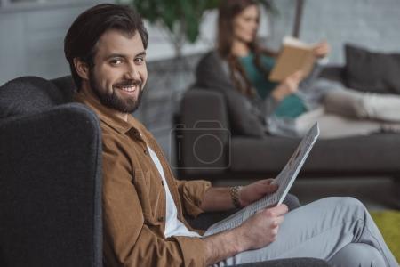 Photo pour Journal de lecture en couple et réservez dans le salon à la maison - image libre de droit