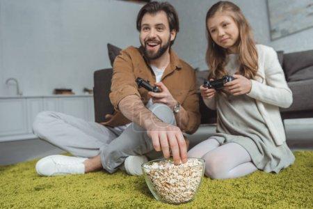 Foto de Padre jugando videojuegos con hija y comer palomitas de maíz - Imagen libre de derechos