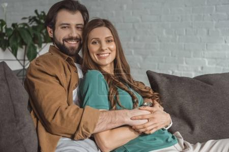 Photo for Smiling boyfriend hugging girlfriend and they looking at camera at home - Royalty Free Image