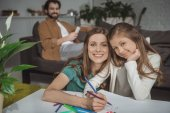 mother helping daughter drawing with felt-tip pens and looking at camera
