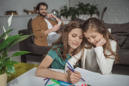 mother helping daughter drawing with felt-tip pens at home