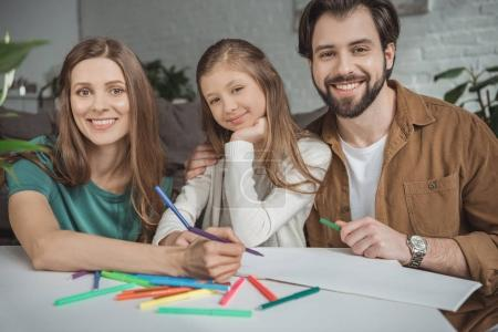 smiling parents and daughter drawing with felt-tip pens and looking at camera