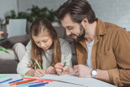 father and daughter drawing with felt-tip pens at home