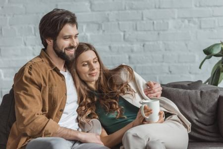 boyfriend hugging girlfriend with cup of coffee at home