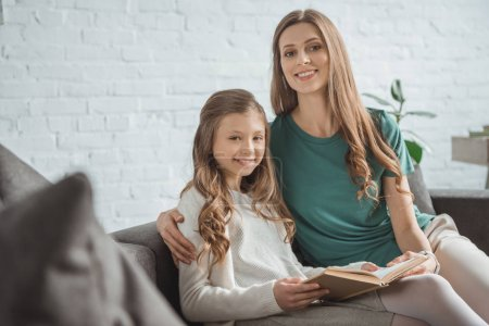mother and daughter holding book and looking at camera at home