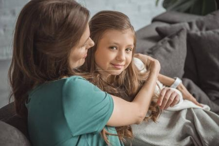 mother hugging daughter on sofa at home