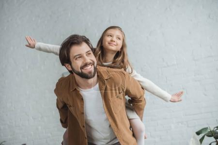 Photo for Happy father giving piggyback to daughter at home and they looking away - Royalty Free Image