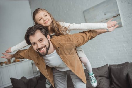 happy father giving piggyback to daughter at home