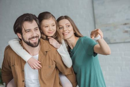happy mother pointing on something to daughter and husband