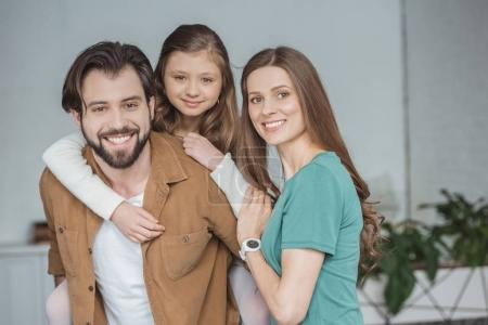 happy parents and daughter looking at camera at home