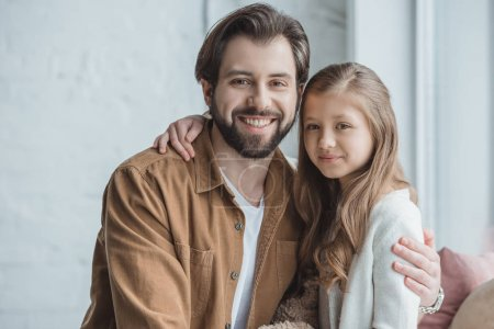 happy father and daughter looking at camera at home