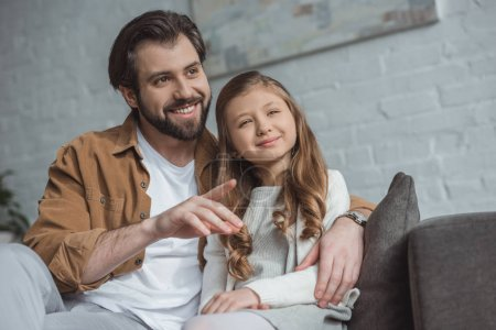 smiling father pointing on something to daughter at home
