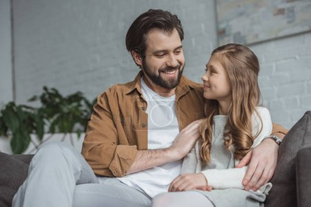 smiling father hugging daughter on sofa at home
