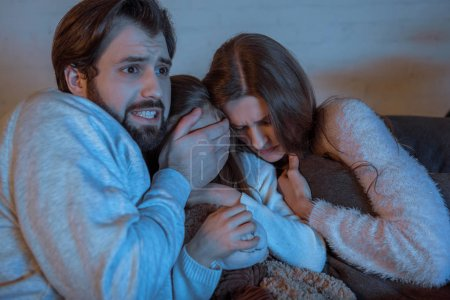 parents and daughter watching horror movie in evening