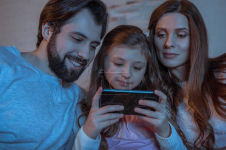 parents looking at daughter using smartphone in evening