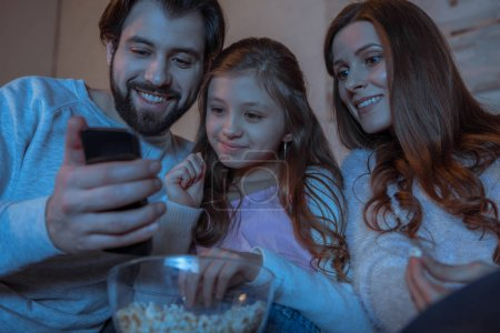 parents and daughter looking at smartphone in evening