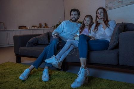 smiling parents and daughter watching tv with popcorn