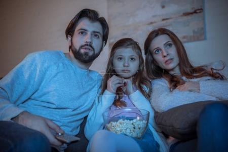 surprised parents and daughter watching movie on sofa with popcorn