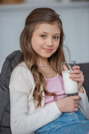 adorable kid holding glass of milk at home