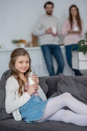 adorable daughter holding glass of milk at home