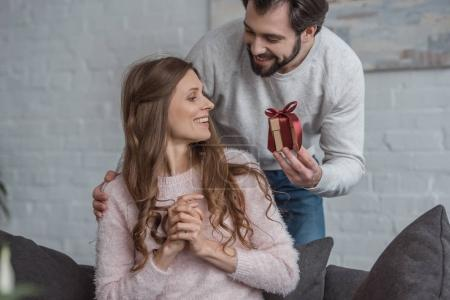 boyfriend presenting gift to girlfriend on international womens day at home