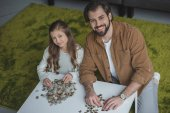 high angle view of father and daughter sitting at table with puzzle pieces and looking at camera