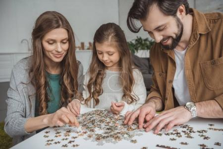 happy parents and daughter connecting puzzle pieces at table