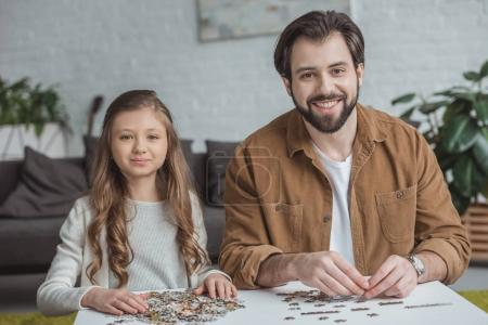 happy father and daughter sitting at table with puzzle pieces and looking at camera