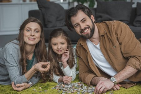 smiling parents and daughter lying on carpet with puzzle pieces and looking at camera