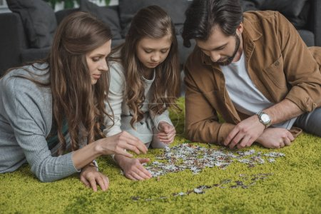 parents and daughter connecting puzzle pieces on floor in living room