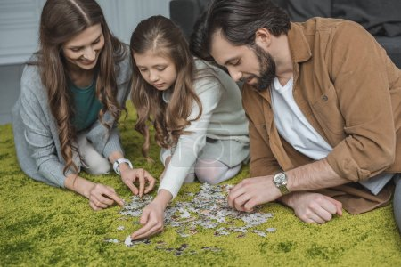 parents and daughter connecting puzzle pieces on carpet in living room