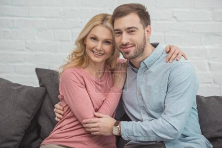 portrait of smiling mother and grown son hugging each other while sitting on sofa