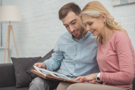 happy family looking at photos in photo album together at home