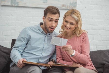 mother and grown son looking at photo in hand while resting on sofa together