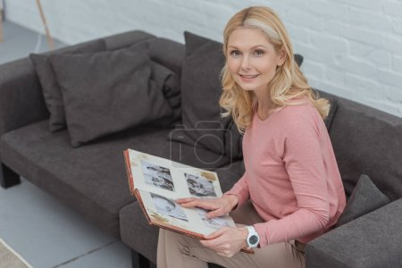 smiling mature woman with photo album resting on sofa at home