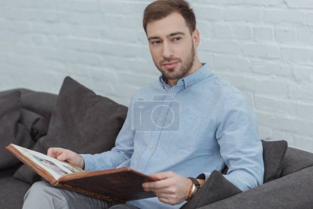 portrait of pensive man with photo album resting on sofa at home