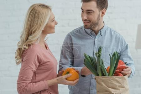 portrait of grown son and mother with paper bag full of fresh vegetables for dinner at home
