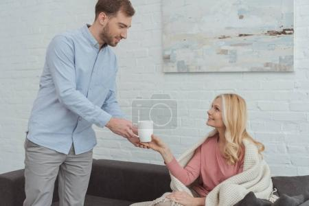 careful grown son brought cup of tea to mother in blanket on sofa at home